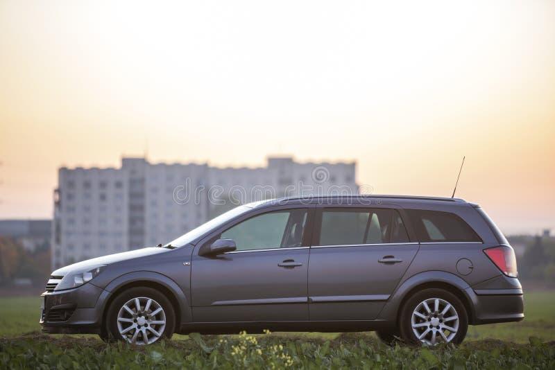 Vista lateral do carro vazio de prata cinzento estacionado no campo na paisagem rural borrada e no céu claro alaranjado brilhante imagem de stock