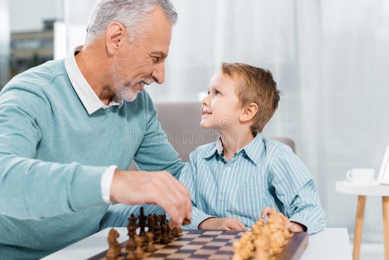 vista lateral do feliz neto e avô olhando um para o outro enquanto jogavam xadrez imagem de stock