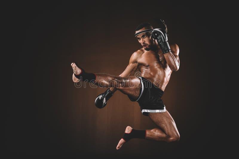 Vista lateral do lutador tailandês muay do trainign irritado em luvas de encaixotamento foto de stock