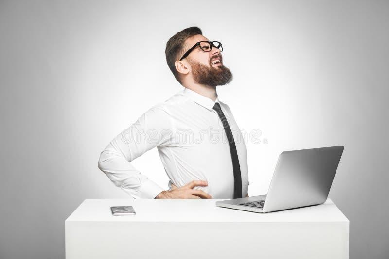 A vista lateral do retrato do gerente novo virado unhealphy na camisa branca e o traje de cerimônia estão sentando-se no escritór imagens de stock