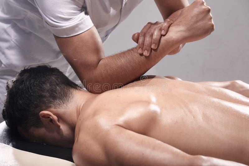 Vista lateral, dois homens novos, 20-29 anos velhos, fisioterapia dos esportes dentro no est?dio, sess?o fotogr?fica Fisioterapeu foto de stock