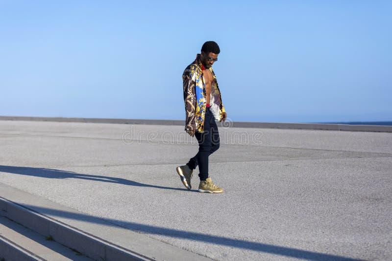 Vista lateral dos óculos de sol vestindo de um homem negro novo que andam contra o céu azul imagem de stock