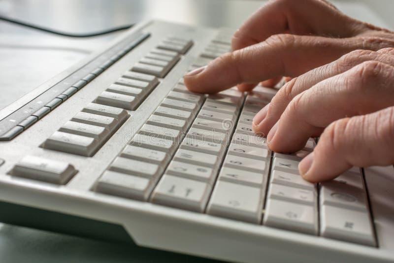 Vista lateral dos dedos que datilografam em um teclado de computador foto de stock