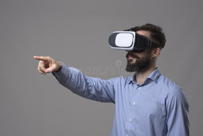 Vista lateral dos vidros vestindo do vr do homem de negócio que outstretching a mão e que apontam o dedo no tela táctil interativ fotos de stock royalty free