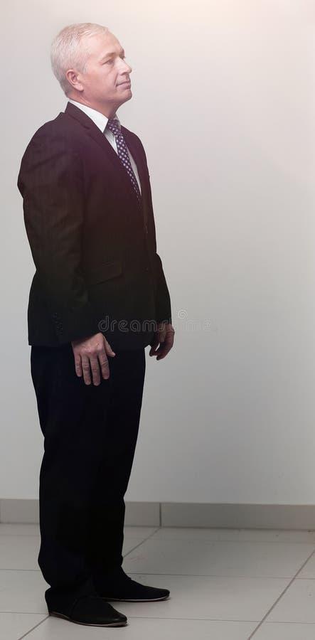 Vista lateral el hombre de negocios mayor está poniendo sus manos en sus bolsillos fotos de archivo libres de regalías