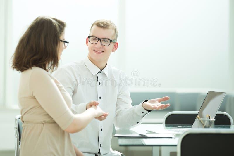 Vista lateral encargado y cliente del apretón de manos en el escritorio de oficina imagen de archivo