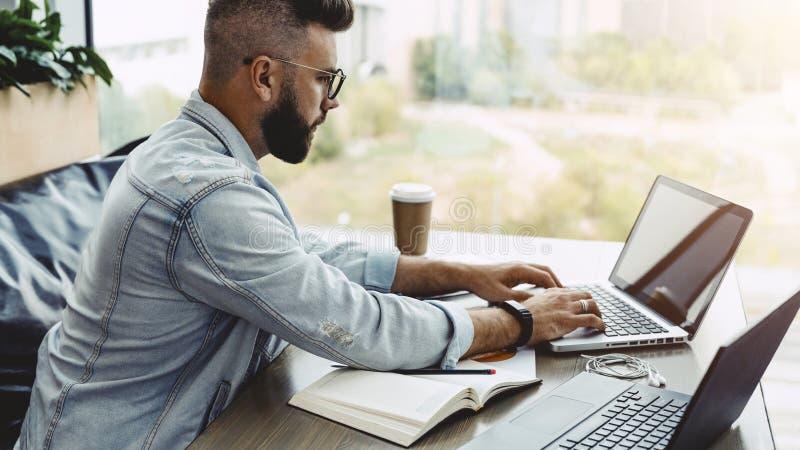 Vista lateral Hombre confiado que trabaja en el ordenador portátil mientras que se sienta en oficina El hombre de negocios enfoca fotografía de archivo