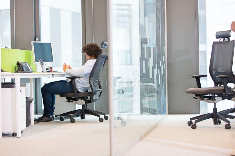 Vista lateral integral del hombre de negocios joven que se sienta en silla en el escritorio en oficina fotografía de archivo libre de regalías