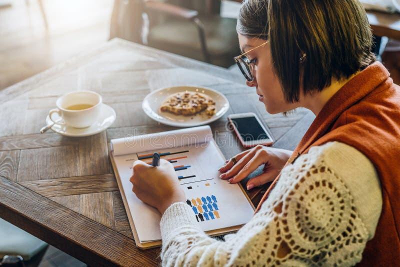 Vista lateral La mujer joven en lentes se está sentando en café en la tabla, trabajando La empresaria está mirando las cartas, gr imagenes de archivo
