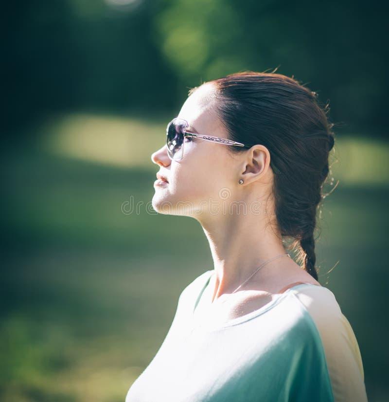 Vista lateral muchacha confiada moderna en gafas de sol fotos de archivo