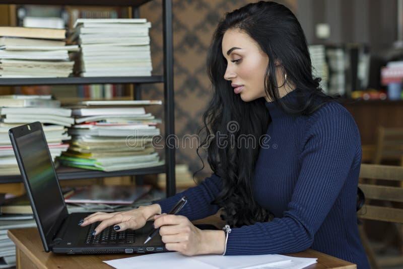 Vista lateral Mujer de negocios joven que se sienta en la tabla y que toma notas en cuaderno En la tabla es el ordenador portátil imágenes de archivo libres de regalías