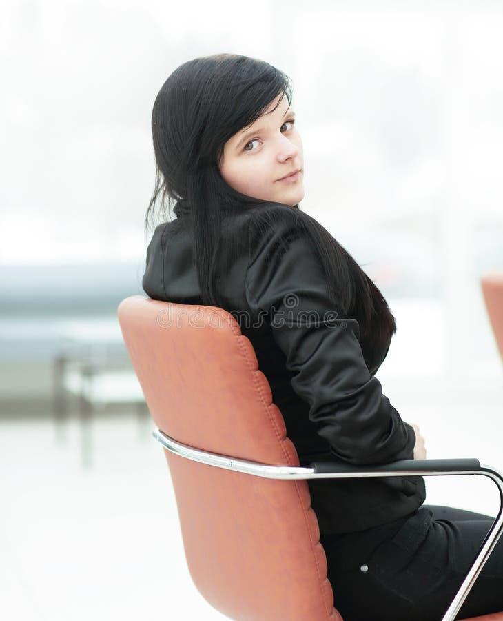 Vista lateral Mujer de negocios joven que se sienta en silla de la oficina fotos de archivo