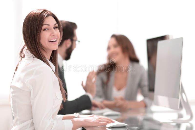 Vista lateral mujer de negocios sonriente que se sienta en el escritorio imagen de archivo