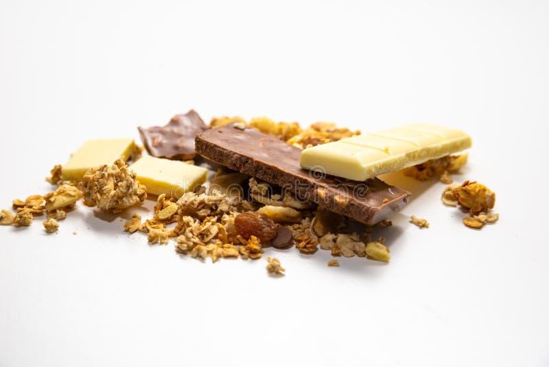 Vista lateral na pilha do muesli do granola/derramada entre o branco barras de chocolate marrons isoladas no fundo branco Equilib imagens de stock