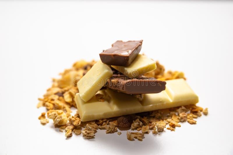 Vista lateral na pilha do muesli do granola/derramada entre o branco barras de chocolate marrons no fundo branco Equilibrado e sa imagem de stock royalty free