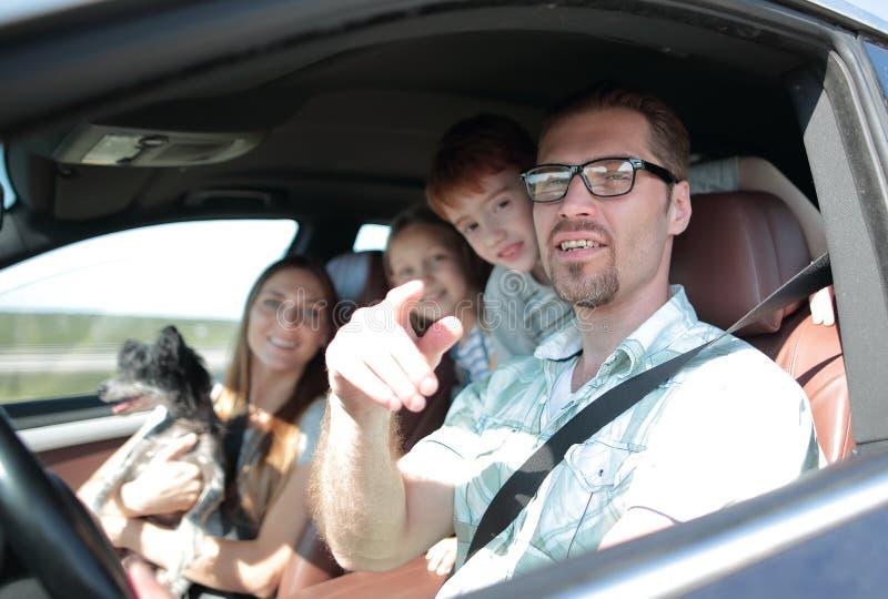 Vista lateral pai feliz que conduz um carro de família imagens de stock