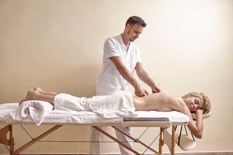 Vista lateral, parte traseira de relaxamento da mulher da massagem do fisioterapeuta, alegria, colocando na cama imagens de stock