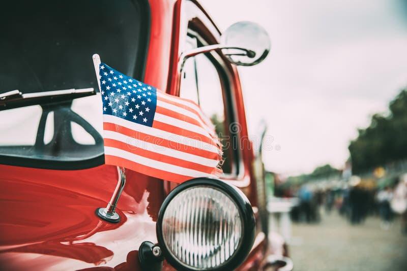 Vista lateral próxima do camionete vermelho com ondulação pequena da bandeira americana fotografia de stock