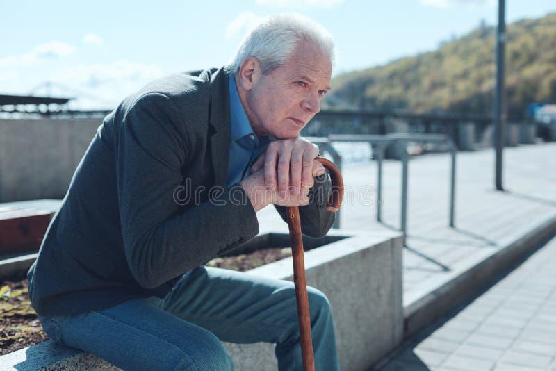 Vista lateral sobre hombre triste con el bastón que mira en vacante fotos de archivo libres de regalías
