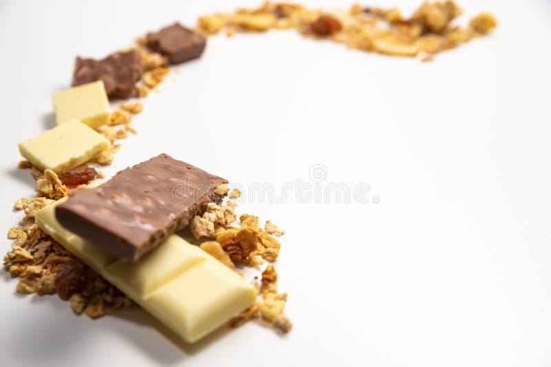 Vista lateral sobre la línea de la trayectoria hecha de muesli del granola/y de las barras de chocolate tajadas blancas, marrones fotos de archivo
