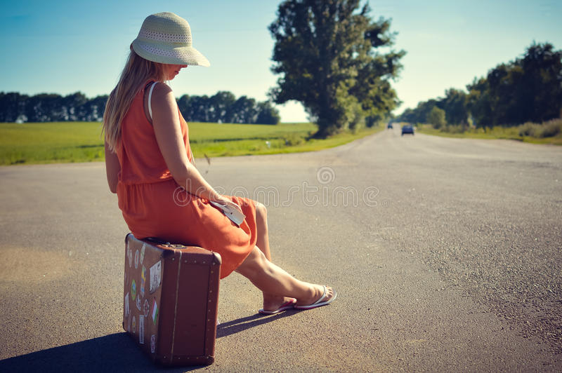 Vista lateral trasera de la mujer bonita joven que hace autostop esperar a lo largo del camino un paseo imagen de archivo libre de regalías