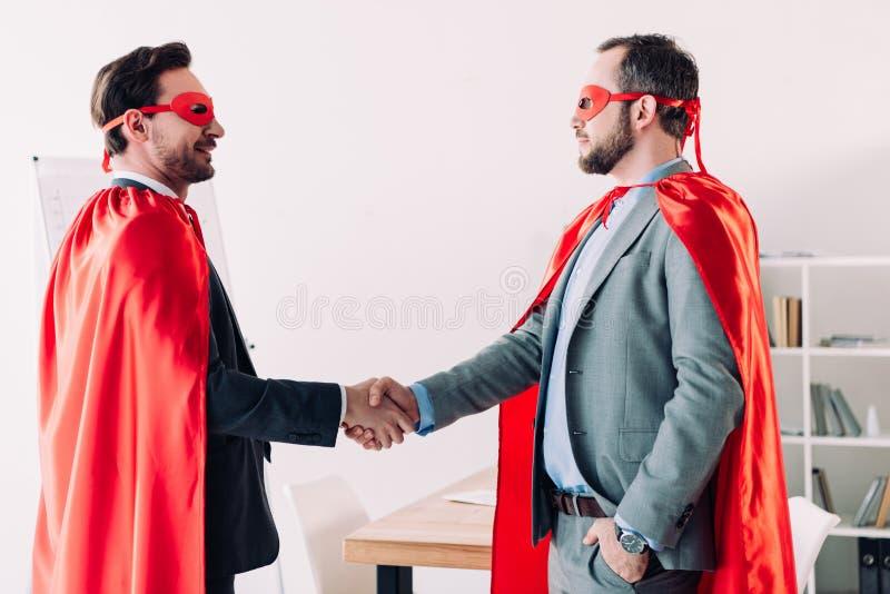 vista laterale degli uomini d'affari eccellenti bei nelle maschere e dei capi che stringono le mani fotografia stock libera da diritti