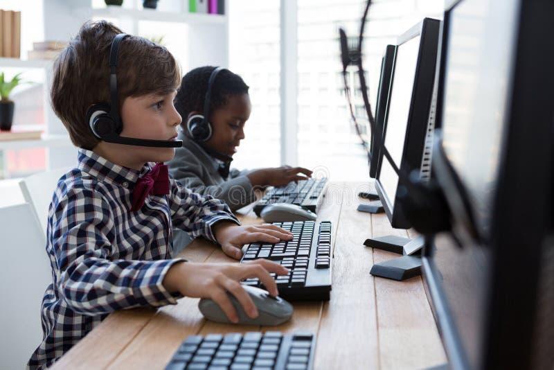 Vista laterale degli uomini d'affari facendo uso del computer mentre parlando tramite la cuffia avricolare allo scrittorio fotografie stock