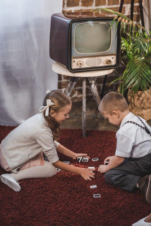 vista laterale dei bambini svegli che giocano insieme i domino a casa fotografia stock libera da diritti