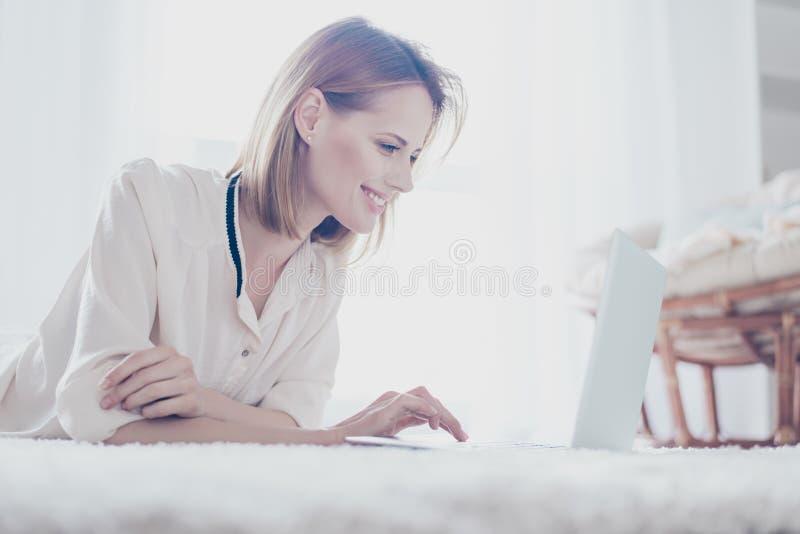 Vista laterale dei vestiti di sorveglianza della donna bionda graziosa facendo uso dei wi fi dentro fotografia stock libera da diritti