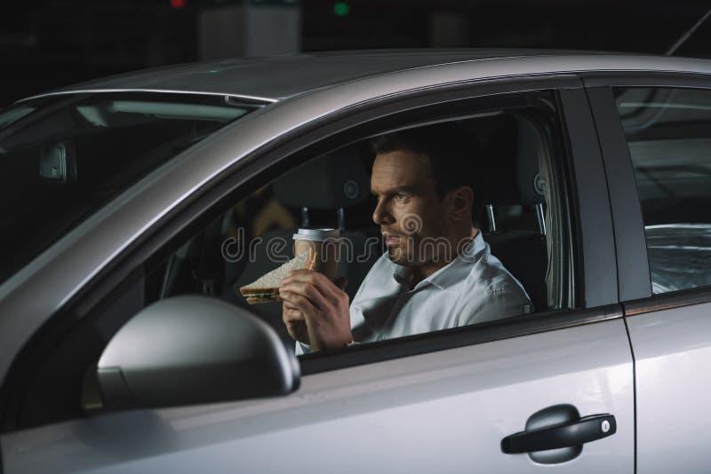 vista laterale del caffè dell'agente investigativo privato e del panino beventi maschii di cibo immagini stock