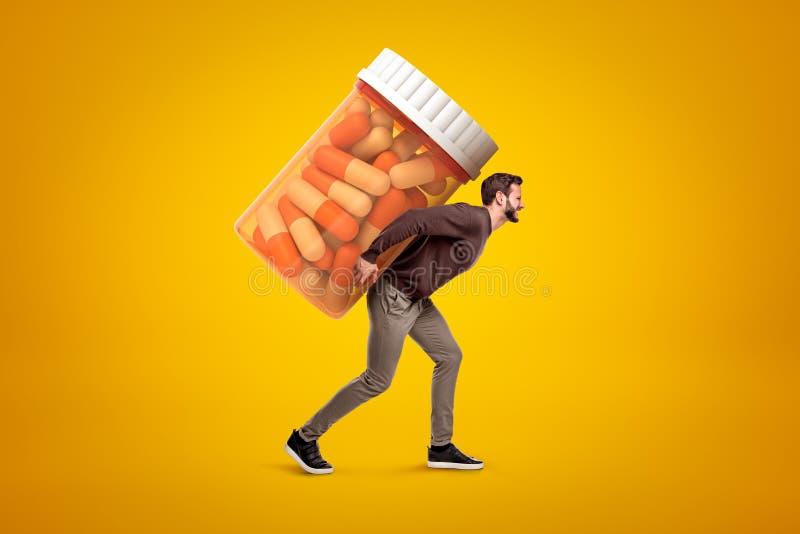 Vista laterale del giovane in abbigliamento casual che porta il grande barattolo pesante di aspetto della medicina su fondo giall fotografia stock libera da diritti