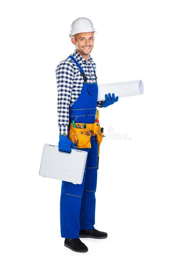 Vista laterale del muratore felice in uniforme con la cassetta portautensili a immagini stock