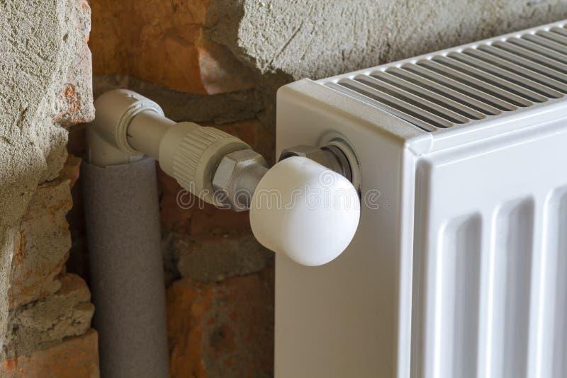 Vista laterale del primo piano del radiatore di riscaldamento installato isolato sul bri immagine stock