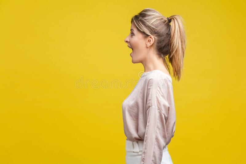 Vista laterale del profilo di una donna bionda felice e felice, con capelli da favola e camicetta di beige, isolata su fondo gial fotografie stock