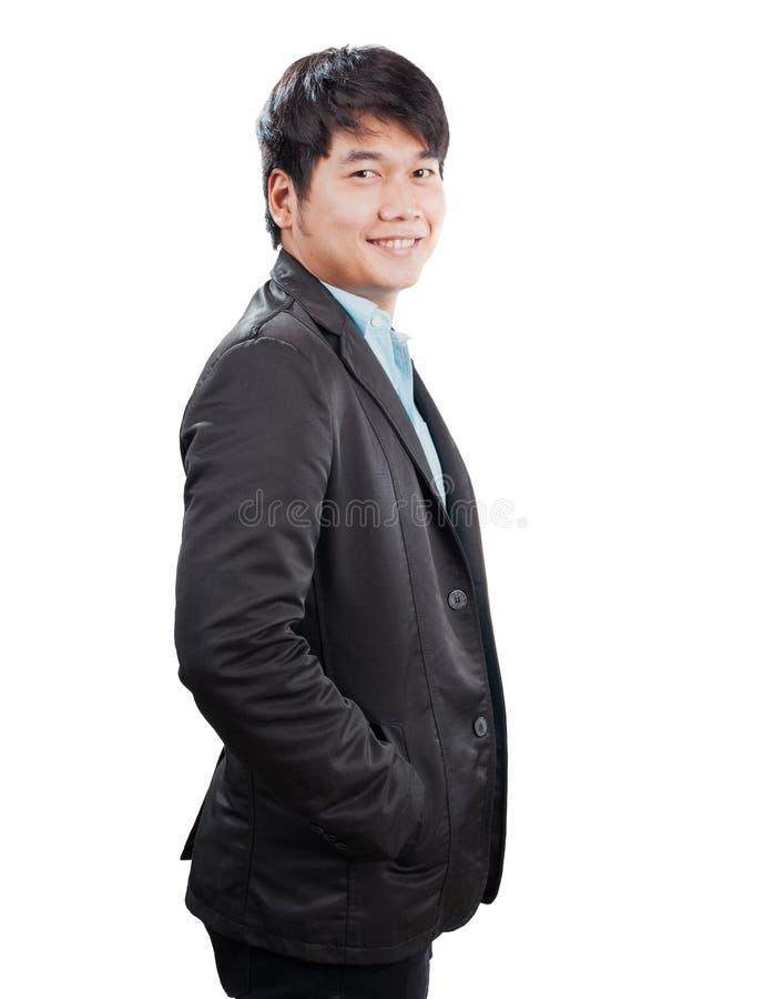 Vista laterale del ritratto di giovane uomo asiatico con la condizione occidentale del vestito fotografie stock