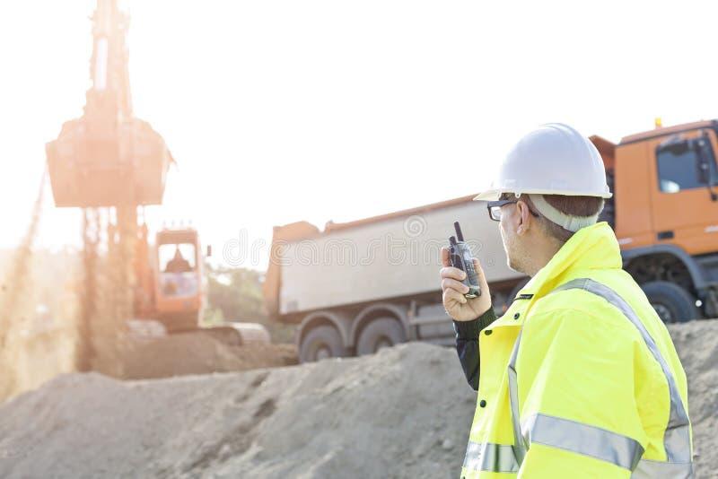 Vista laterale del supervisore che per mezzo del walkie-talkie al cantiere contro il chiaro cielo immagini stock