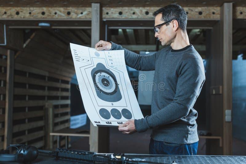 vista laterale del tiratore che esamina obiettivo usato dopo la fucilazione fotografia stock libera da diritti