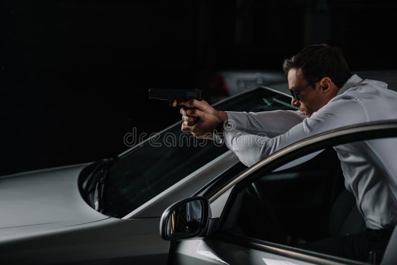 vista laterale dell'agente maschio clandestino nella tendenza degli occhiali da sole fotografie stock
