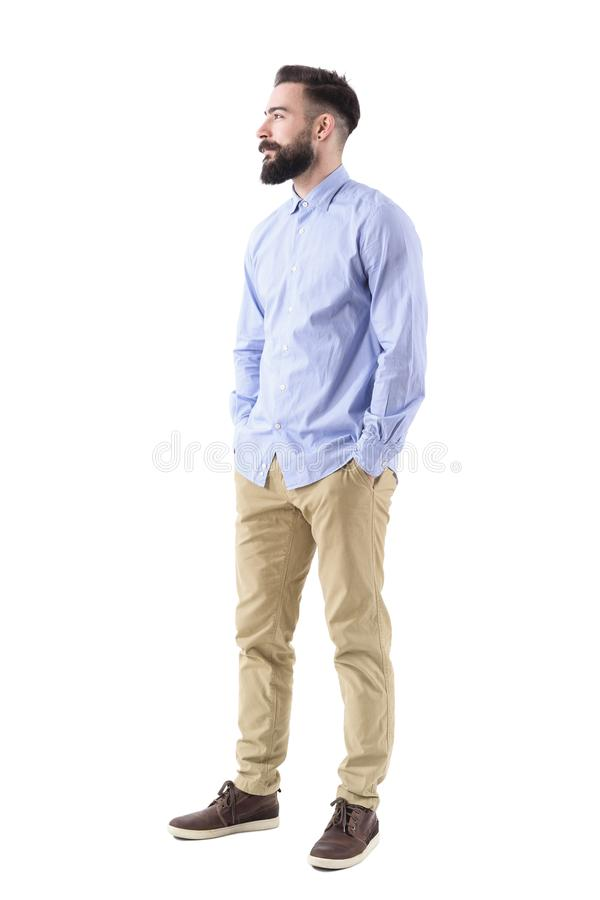 Vista laterale dell'uomo barbuto bello elegante di affari che cerca sorridente con le mani in tasche immagine stock