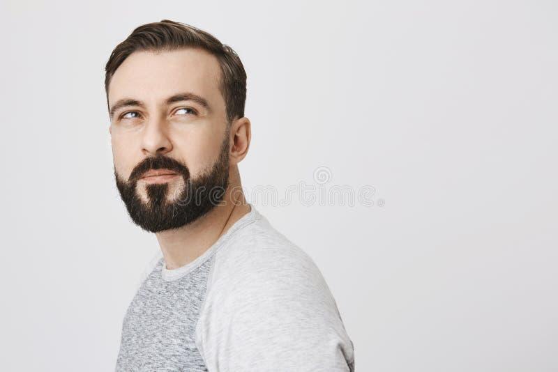 Vista laterale dell'uomo barbuto premuroso attraente, girata per guardare sospettoso qualcosa, stando contro il gray fotografia stock