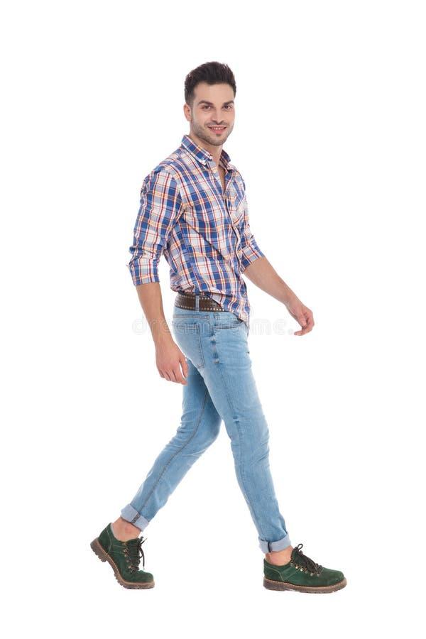 Vista laterale dell'uomo casuale con fare un passo della camicia di plaid fotografia stock libera da diritti