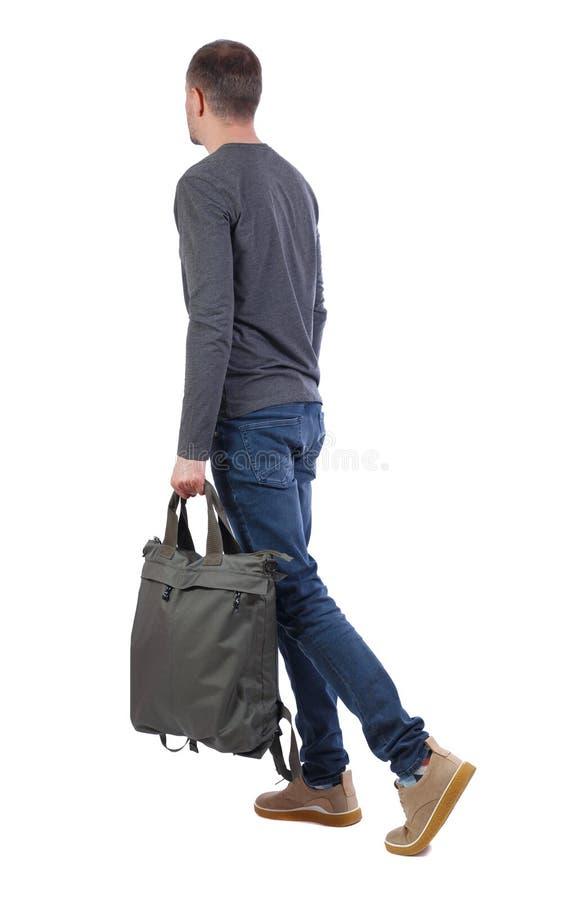 Vista laterale dell'uomo di camminata con la borsa verde punto di vista della parte della persona immagini stock