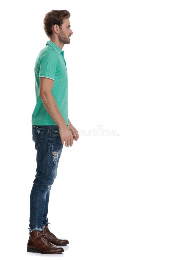 Vista laterale dell'uomo nel polo verde che aspetta nella linea fotografia stock libera da diritti