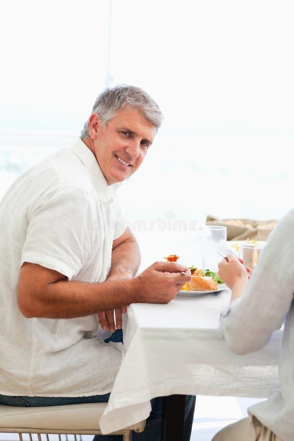 Vista laterale dell'uomo sorridente che ha pranzo immagini stock libere da diritti