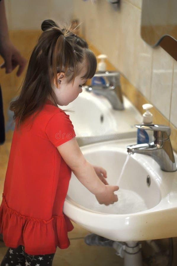Vista laterale della bambina sveglia che lava le sue mani nell'asilo, scuola immagini stock libere da diritti
