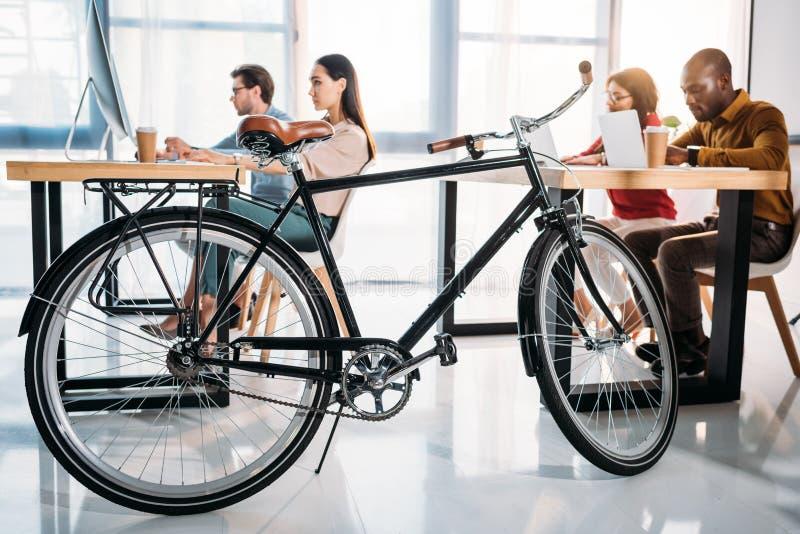 vista laterale della bicicletta e della gente di affari multiculturale di lavoro fotografia stock libera da diritti