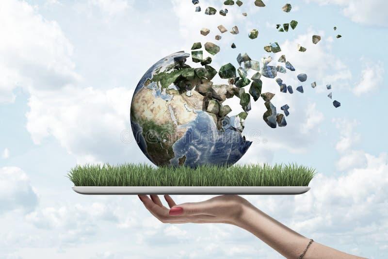 Vista laterale della compressa della tenuta della mano della donna con erba verde sullo schermo e sul globo della terra sulla cim immagine stock libera da diritti