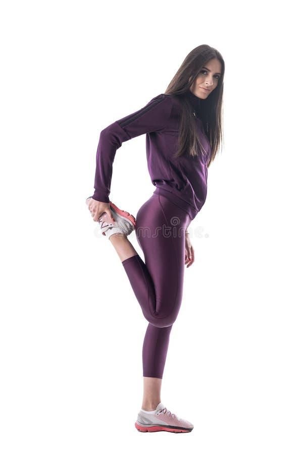 Vista laterale della donna adatta sportiva che esercita e che allunga i muscoli della gamba che esaminano macchina fotografica fotografie stock