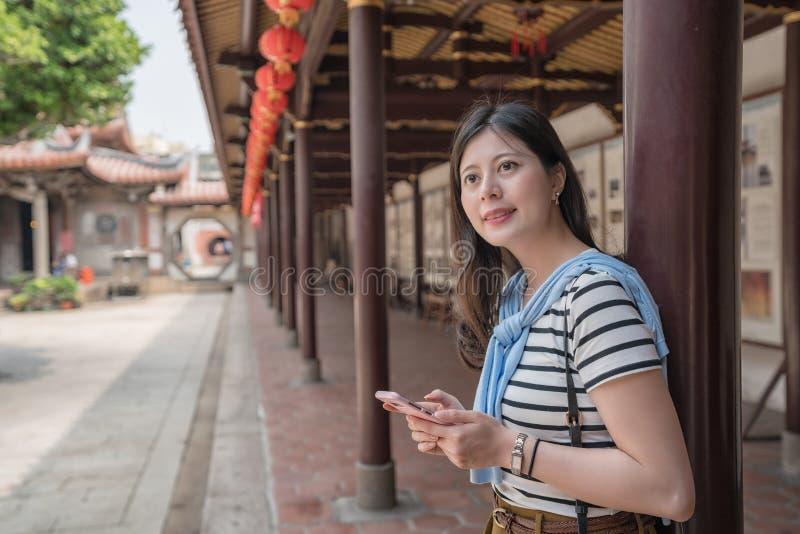 Vista laterale della donna asiatica che tiene uno smartphone fotografia stock libera da diritti