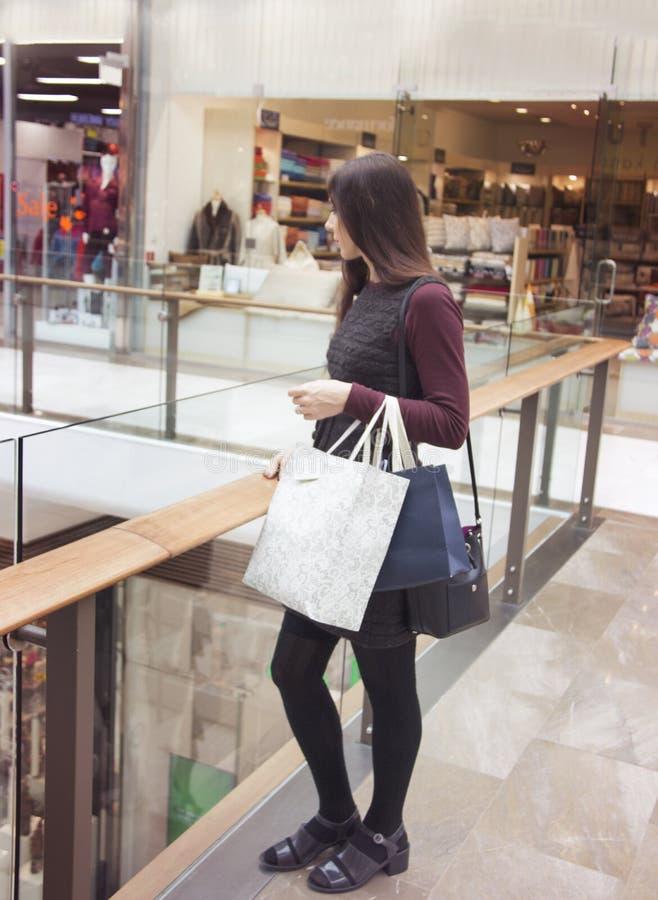 Vista laterale della donna attraente alla moda che sta nell'interno del centro commerciale con i sacchetti della spesa fotografie stock